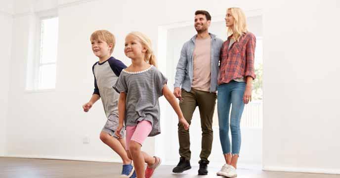 Immobilie vermieten: Mieter, Familie mit 2 Kindern, laufen in eine frisch gemietete Mietwohnung