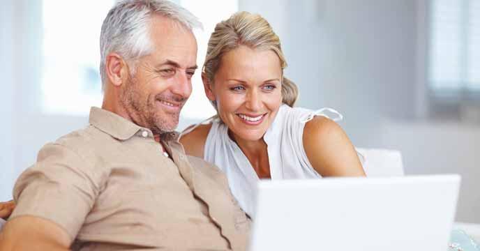 Vermieterin einer Immobilie sitzt mit Ihrem Mann glücklich und lächelnd vor dem Computer und freuen sich über die erfolgreiche Vermietung ihrer Immobilie