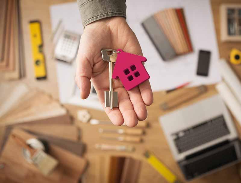 Tippgeber: Schreibtisch eines Maklers mit einer Hand eines Maklers mit einem Hausschlüssel