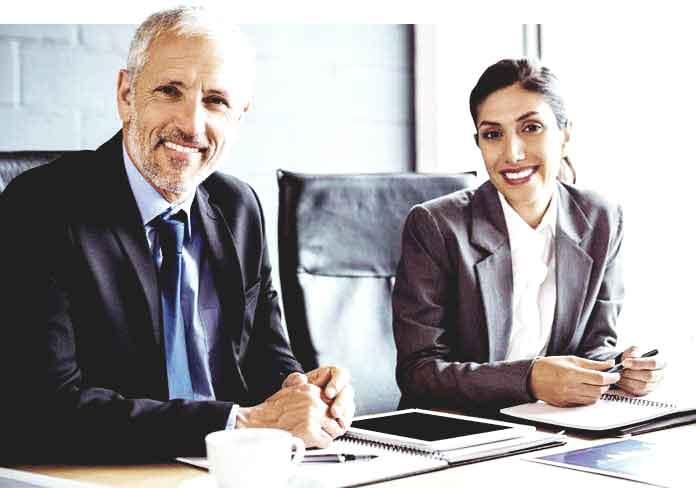 Ein Immobilienmakler und eine Immobilienmaklerin sitzen in Hamburg bei der Arbeit im Büro und lächeln