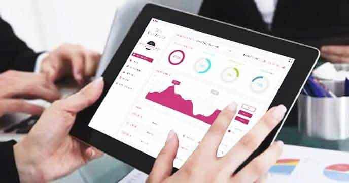 Makler sitzt in Hamburg im Büro und nutzt modernste Software für eine Datenanalyse für den Verkauf einer Immobilie