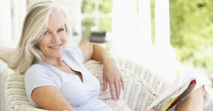 Immobilienverkäuferin (Frau) liegt auf der Couch Zuhause und lächelt glücklich