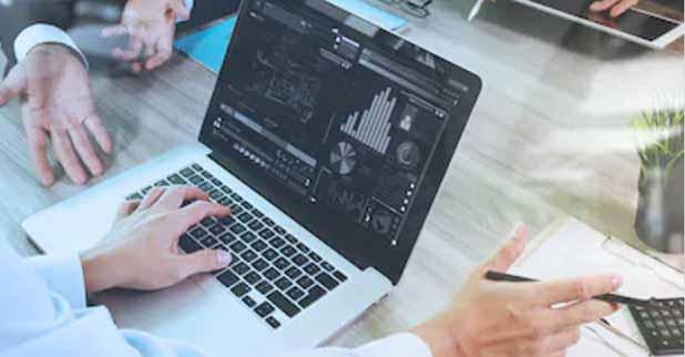 Makler sitzt im Büro am Computer und nutzt modernste Software, um den optimalen Wert einer Immobilie zu ermitteln
