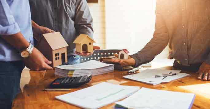 Die Grundstücksbewertung: Architekten, Makler und Bauherren nehmen Grundstücksbewertung vor an einem Tisch.