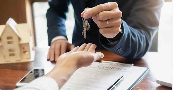 Eigentumswohnung kaufen: Käufer einer Eigentumswohnung bekommt die Wohnungsschlüssel vom Makler überreicht