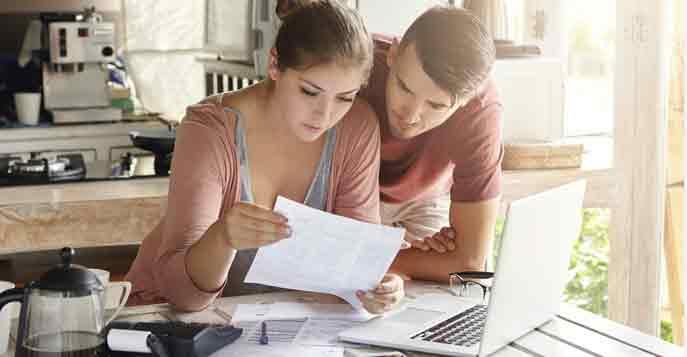Zwei Immobilienkäufer sehen am Schreibtisch Unterlagen zur Grunderwerbssteuer ein
