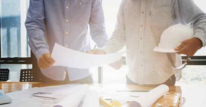 Grundstück verkaufen: Makler und Architekt planen am Tisch die Bebauungsmöglichkeiten
