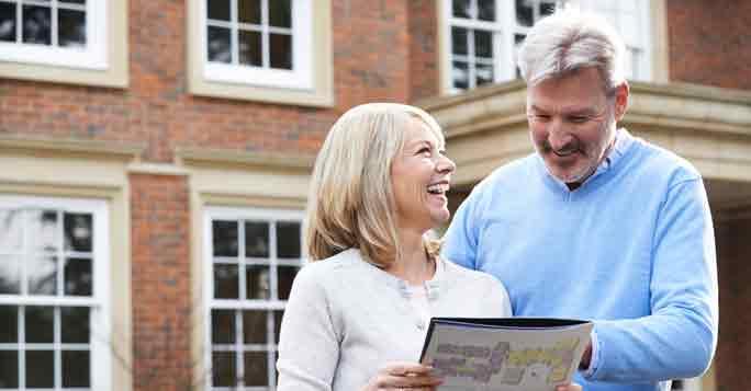 Haus verkaufen: Hausverkäufer stehen vor ihrem Haus mit einer Immobilienbewertung in ihren Händen