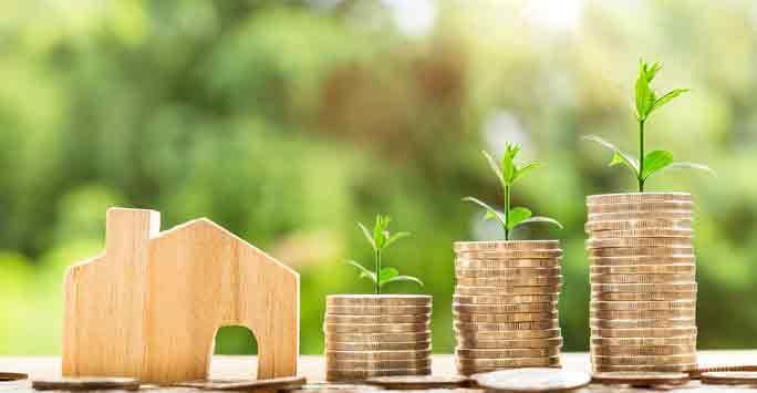 Gesparte Steuern als Kleingeld und ein Haus aus Holz daneben