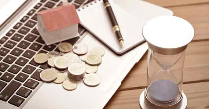 Laptop,Taschenrechner, Stiift und Zettel, um den Zeitwert einer Immobilie zu berechnen