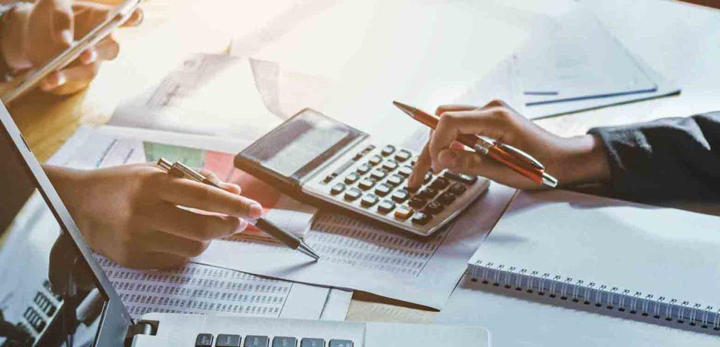 Verkäufer und Makler berechnen Ertragswert um eine vermietete Wohnung zu verkaufen