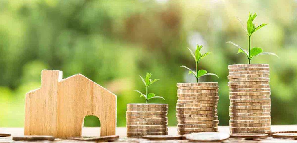 Hausverkauf Steuern: Geld liegt vor einem Holzhaus